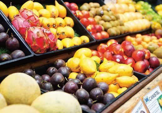 罗伯特和太太在果 园门口经营的小水果摊,同到访游客分 享自家种植的热带水果