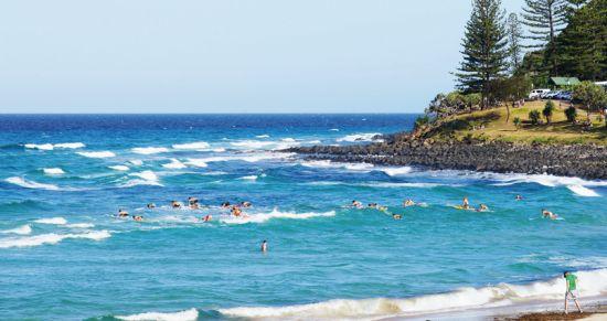 一群初学者正跪在冲浪板上,面对一波波逼近的 浪花努力地平衡身体